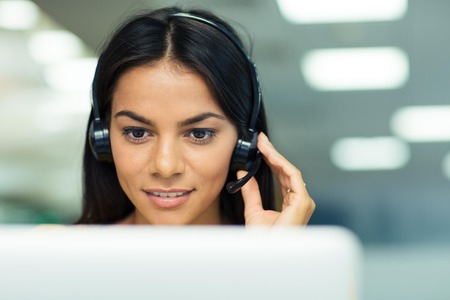 customer support: Happy businesswoman working on laptop with headphones in office