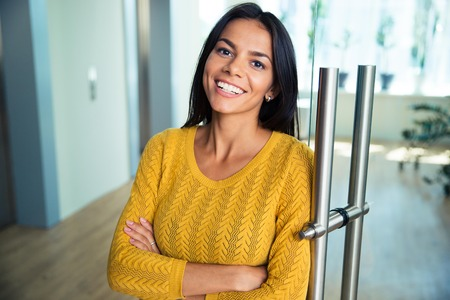 Portret van een vrolijke ongedwongen zakenvrouw staan met de armen gevouwen in kantoor