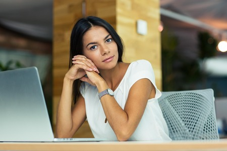 mujer pensativa: Portrait of attractive thoughtful businesswoman sitting at the desk in office and looking at camera