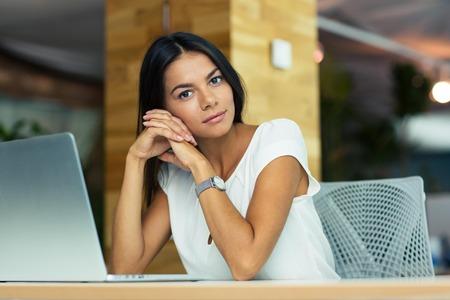 mujer pensativa: Retrato de atractiva empresaria reflexiva sentado en el escritorio en la oficina y mirando a la cámara