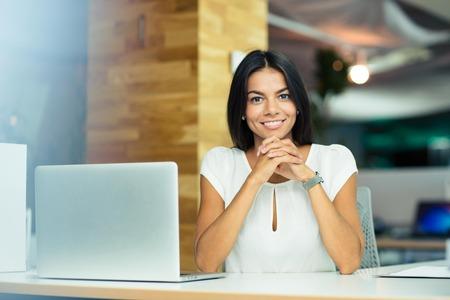 persona sentada: Retrato de una alegre mujer de negocios sentado a la mesa en la oficina y mirando a c�mara