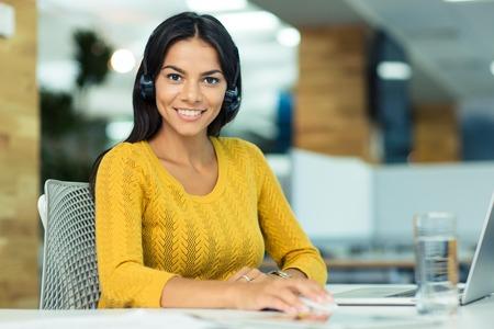 彼女の職場のオフィスで座っていると、カメラ目線のヘッドフォンで陽気な実業家の肖像画 写真素材
