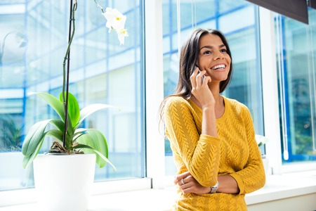 Laughing casual businesswoman talking on smartphone in office near window and looking away