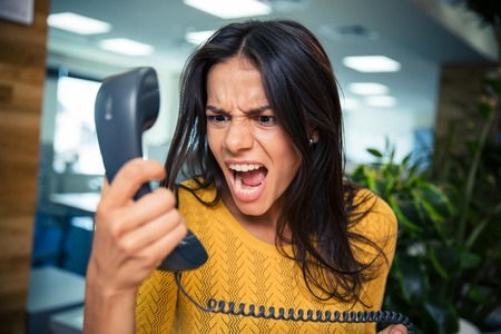 Angry businesswoman shouting on phone in office Foto de archivo