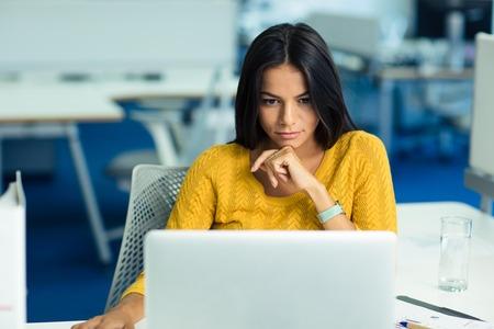 オフィスでラップトップ コンピューターを使用してのセーターでカジュアルな若い実業家の肖像画 写真素材