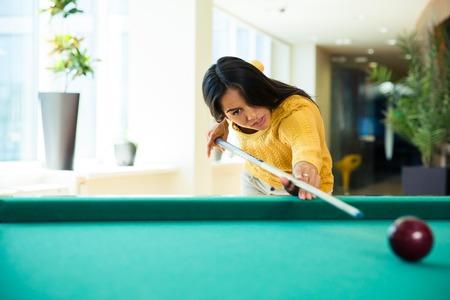 billard: Beautiful young woman playing billiards indoors Stock Photo