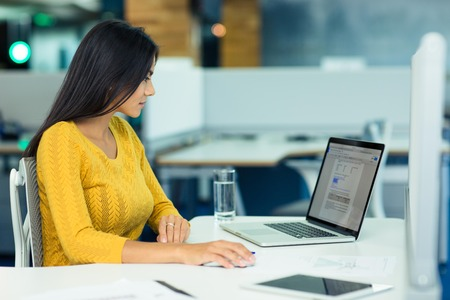 working attire: Young casual businesswoman using laptop in office