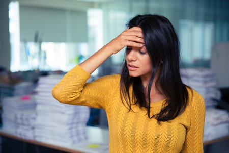 attractive office: Portrait of a casual businesswoman having headache in office