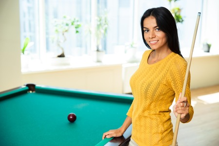 billard: Happy young woman playing billiards indoors Stock Photo