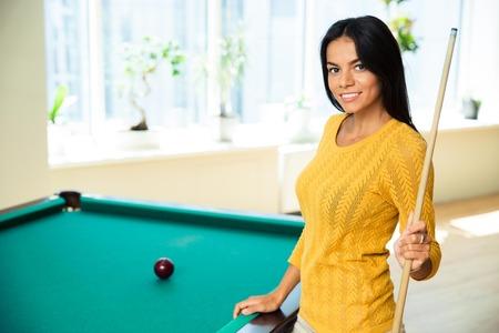 billard: Happy young woman playing billiards indoors Stock Photo