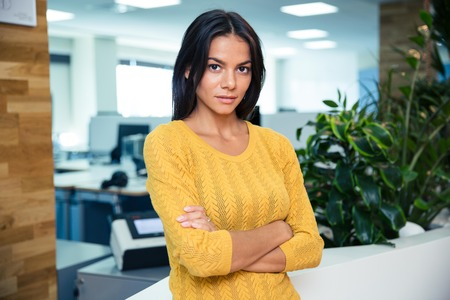 Portrait of a serious casual businesswoman standing with arms folded in office and looking at camera