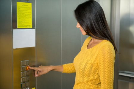 lift hands: Portrait of a casual businesswoman pushing elevator button in office