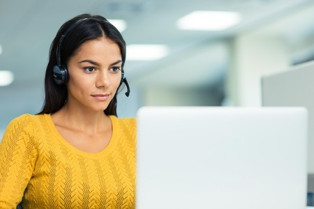 Portrait of a young businesswoman in headphones using laptop in office Stock Photo