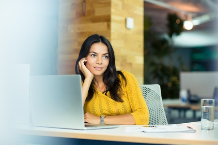 woman  laptop: Portrait of a happy thoughtful businesswoman sitting at the table in office and looking away Stock Photo