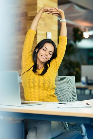 office break: Portrait of a happy businesswoman sitting at the table and stretching hands in office Stock Photo