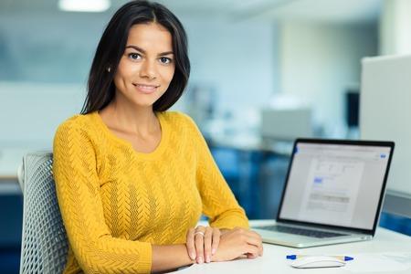Portret van een gelukkig casual zakenvrouw in trui zit op haar werkplek in het kantoor