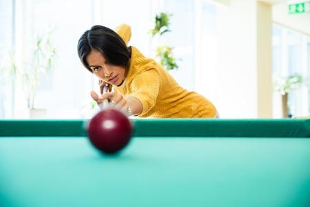 billard: Charming woman playing billiards indoors Stock Photo