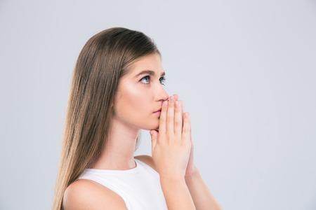 祈る少女の肖像は、白い背景で隔離。見上げてください。 写真素材