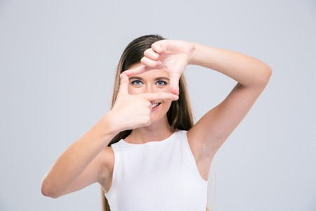 looking through frame: Portrait of a happy female teenager looking at camera through frame gesture isolated on a white background Stock Photo
