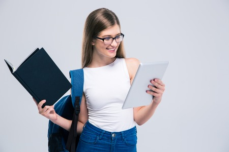 surf girl: Portrait of a cheerful female teenager with backpack and book using tablet computer isolated on a whtie background
