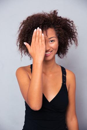 Portret van een glimlachende afro Amerikaanse vrouw die haar oog behandelt en camera over grijze achtergrond bekijkt