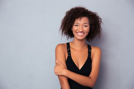 Portrait of a happy black african woman standing over gray background
