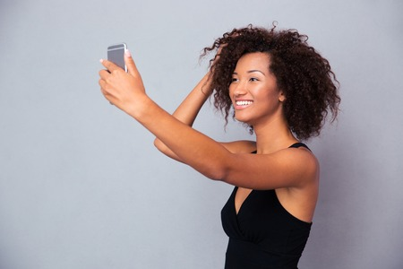 attractive women: Portrait of a smiling afro american woman making selfie photo on smartphone over gray background