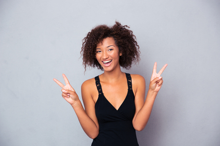 victory sign: Portrait of a happy african woman showing victory with fingers over gray background and looking at camera