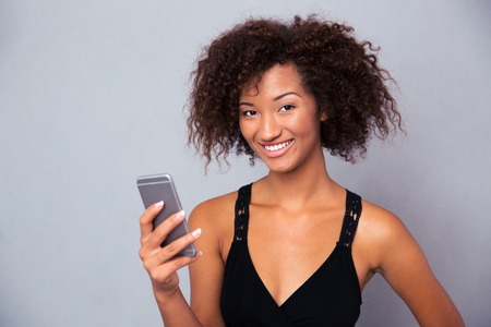 afro girl: Portrait of a smiling afro american woman using smartphone over gray background