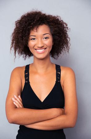 Glimlachende Afrikaanse vrouw met armen gevouwen op een grijze achtergrond Stockfoto