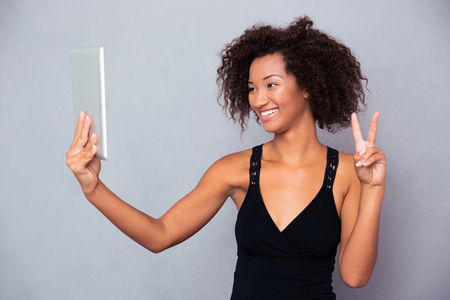 Portrait of a smiling afro american woman making video call on tablet computer over gray background Stock Photo