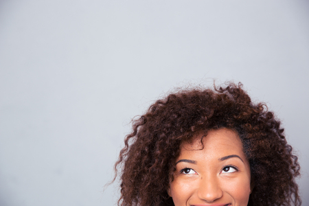 woman looking up: Cropped image of african woman looking up at copyspace over gray background