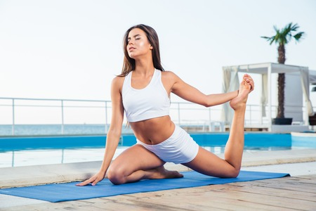 beach mat: Portrait of a young woman doing yoga exercises outdoors