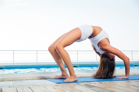 dwi: Young girl standing in bridge pose outdoors Stock Photo