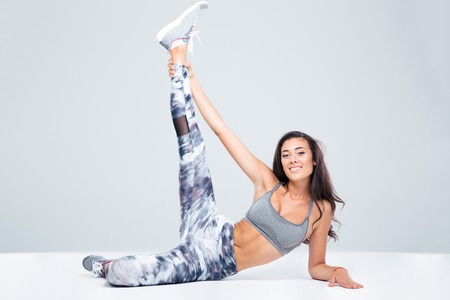 hamstrings: Portrait of smiling fitness woman stretching legs on the floor isolated on a white background