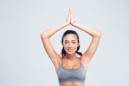 manos unidas: Mujer feliz de la aptitud con las manos juntas sobre la cabeza aislado en un fondo blanco. Mirando a la cámara