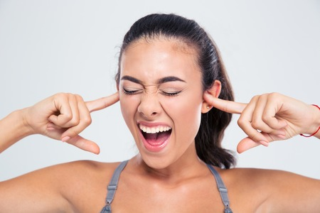 bad hair: Portrait of a fitness woman covering her ears with fingers and shouting isolated on a white background