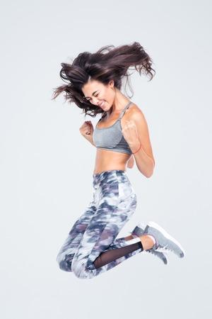 Pleine longueur portrait d'une femme de remise en forme gai saut isolé sur un fond blanc Banque d'images - 44276835