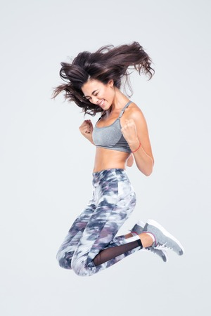 Full length portrait of a cheerful fitness woman jumping isolated on a white background