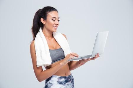 Retrato de una mujer feliz de la aptitud con la toalla que usa el ordenador portátil aislado en un fondo blanco