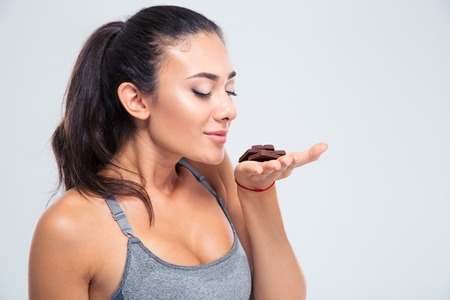 yummy: Portrait of a pretty girl smelling chocolate isolated on a white background