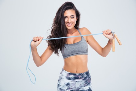 skipping rope: Portrait of a charming woman holding skipping rope isolated on a white background