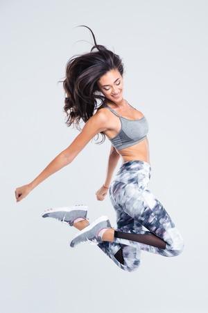 gente saltando: Retrato de cuerpo entero de la mujer sonriente deportiva saltando aislado en un fondo blanco