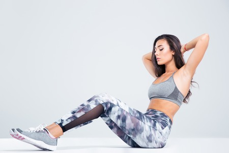 Portrait of a fitness woman doing abs exercises isolated on a white background