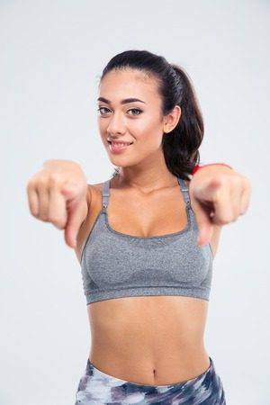 Portrait of a happy fitness woman pointing finger at camera isolated on a white background