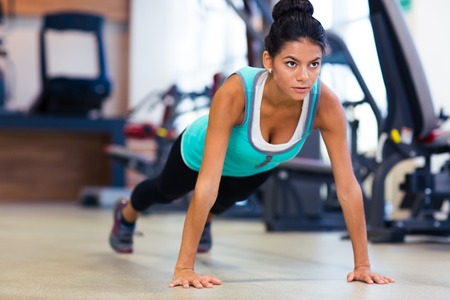 ups: Sports woman doing push ups in fitness gym