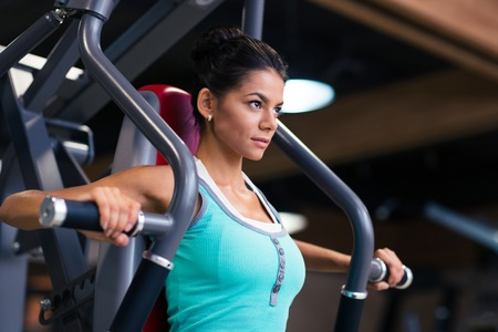 Portrait of a sports woman workout on exercises machine at fitness gym