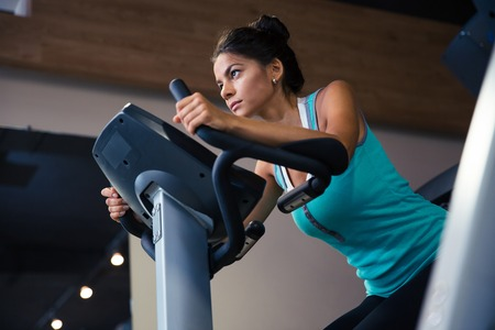 pretty: Pretty woman workout on exercises machine in fitness gym