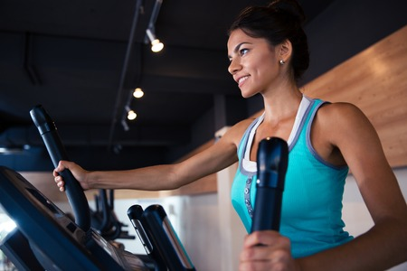cardio workout: Happy woman workout on exercises machine in fitness gym Stock Photo