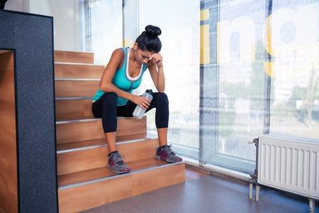 gimnasio: Cansado mujer sentada en las escaleras con la botella de agua en el gimnasio Foto de archivo
